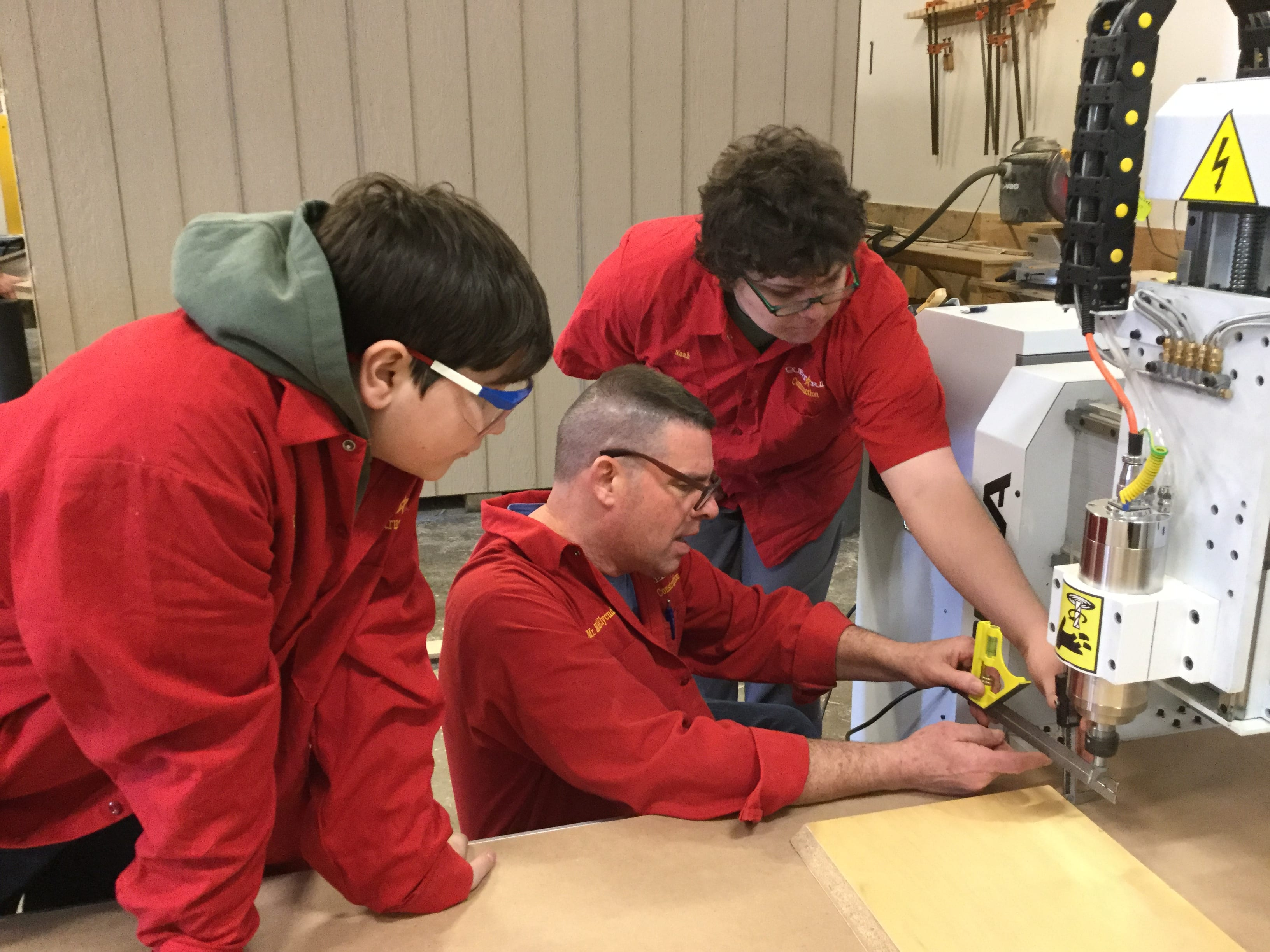 Image of three people in red workshirts working together on a CNC machine